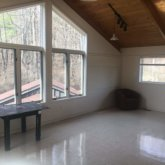 visual arts studio with vaulted ceiling, large windows, and a vinyl tile floor
